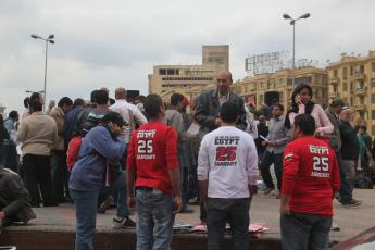 "Demonstrators sell ""The Day We Changed"" T-shirts while protesters gather in Cairo's Tahrir Square."