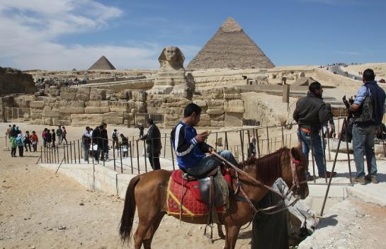 A man renting a horse waits for tourists in front of the Sphinx, the Chephren Pyramid, and the Mycerinus Pyramid.