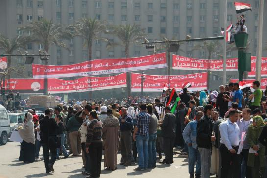 Protesters hold banners in Cairo's Tahrir Square on the day before a countrywide vote on constitutional amendments.
