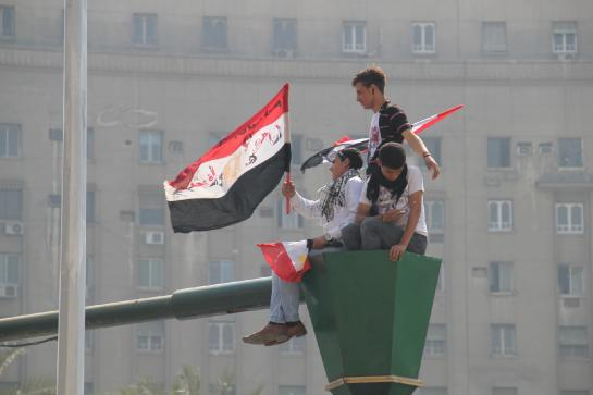 Teenagers wave a flag above Cairo's Tahrir Square on the day before a countrywide vote on constitutional amendments.