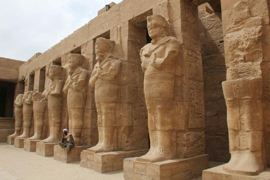 An Egyptian man sits in front of the Temple of Ramses III in Karnak's Temple of Amun.