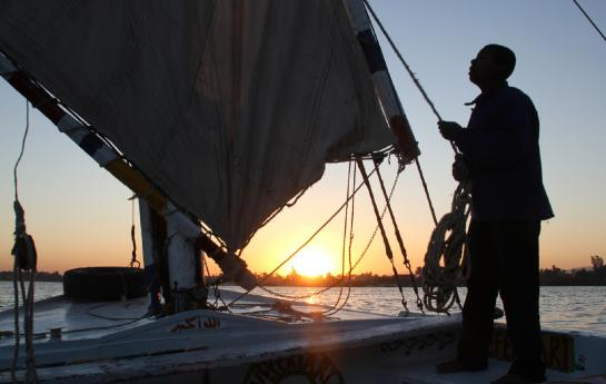 A felucca captain adjusts the sail on his boat on the Nile River at sunset.