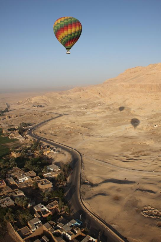 A hot air balloon floats above the Theban Necropolis on the Nile's west bank near Luxor, Egypt.