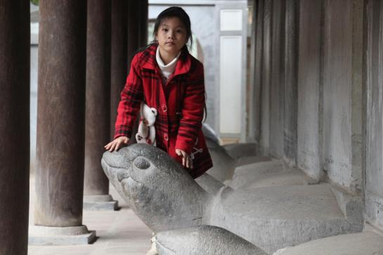 A young girl rubs the head of a statue of the Hoan Kiem turtle in Hanoi's Temple of Literature.