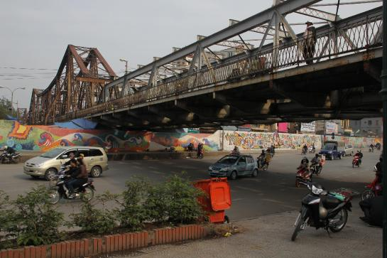 Traffic and a mural pass under Hanoi's historic Long Bien Bridge.
