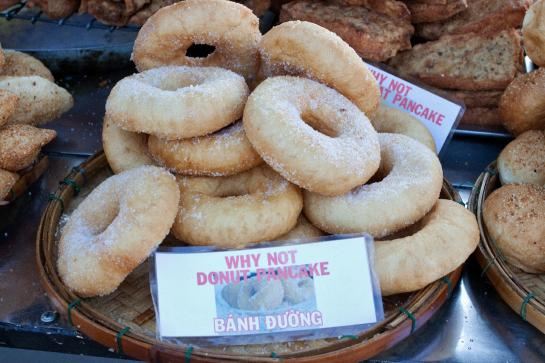 "A ""WHY NOT DONUT PANCAKE"" sign sits in front of donuts for sale in Hoi An, Vietnam."