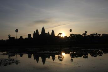 The sun rises behind Angkor Wat early in the morning in Angkor, Cambodia.