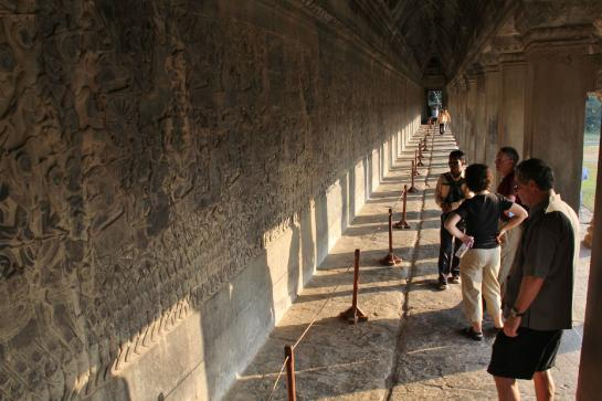 Tourists look at the beautiful and intricate bas-reliefs in Angkor Wat.