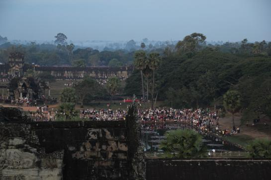 Tourists, as seen from the top of Angkor Wat, gather around the temple's reflection pool.