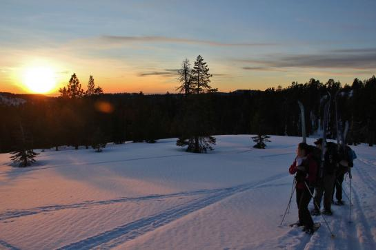Skiers watch the sunset from Yosemite's Heart Attack Hill.