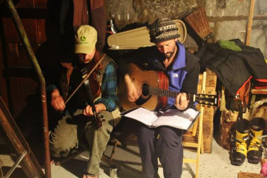 Caretakers at the Ostrander ski hut treat guests to a fiddle and guitar concert.