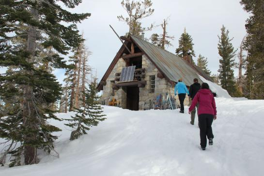 Hikers walk toward Yosemite's Ostrander Ski Hut.