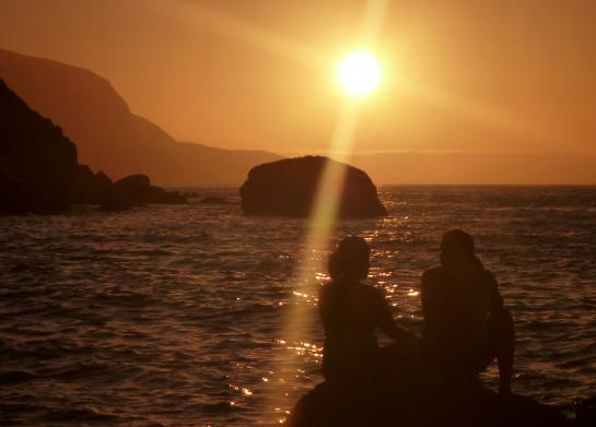 Kayakers relax on a rock at sunset on Catalina Island.