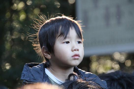 A Japanese boy sits on his father's shoulders, waiting to enter the Meiji Jingu Shrine.