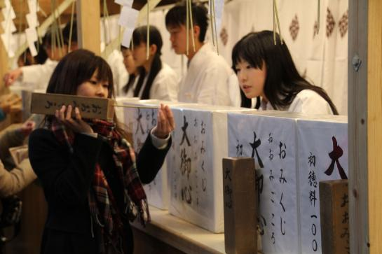 A woman uses a wooden box filled with random numbers to determine which omikuji she'll receive.