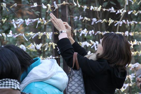 A woman hangs a folded omikuji on a wire fence.