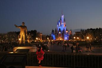 A young Japanese girl looks at Cinderella's Fairy Tale Hall in Tokyo Disneyland at night.