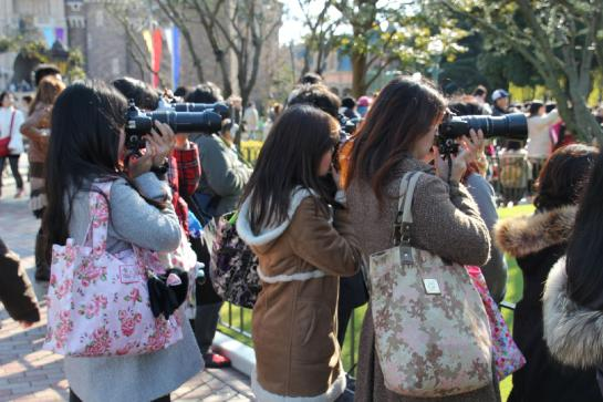 Women take photos of a parade at Tokyo Disneyland.