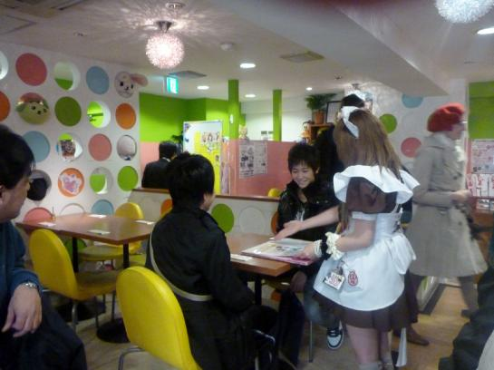 A Japanese girl dressed as a maid waits on boys in a maid cafe in Akihabara, Tokyo, Japan.