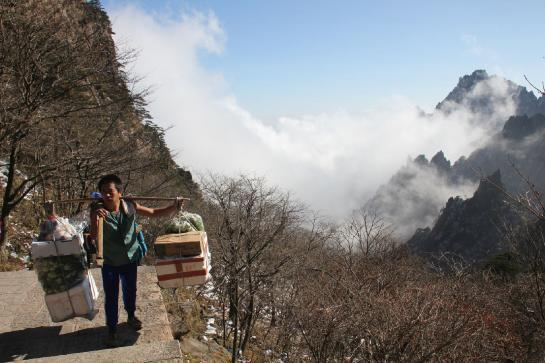A porter carries food and supplies to hotels atop Huangshan.