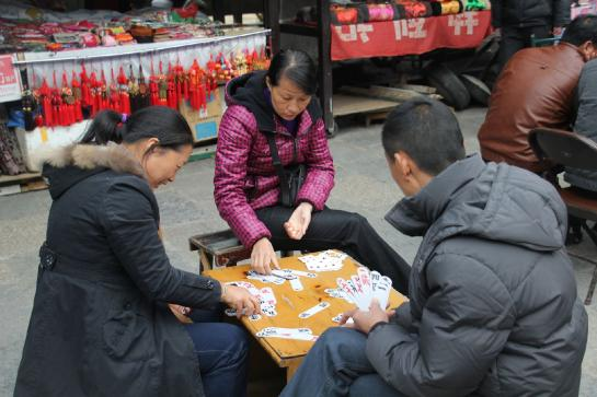 Chinese vendors play cards while waiting for customers in Yángshuò.