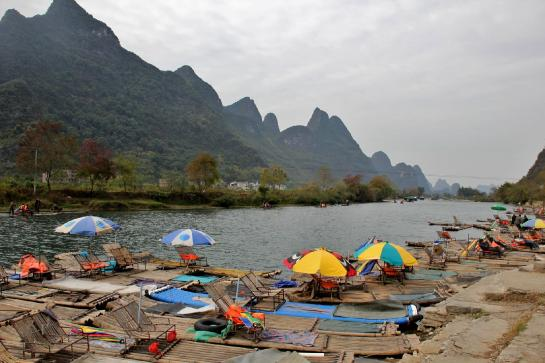 Bamboo rafts wait for tourists on the Yulong River in Yángshuò, Guăngxī, China.