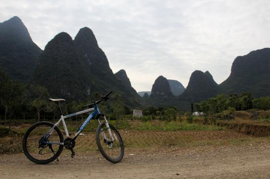 A bicycle sits in front of the otherworldy karsts of Yángshuò, Guăngxī, China.