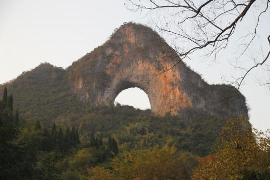 Orange light makes Moon Hill glow at sunset near Yángshuò, Guăngxī, China.