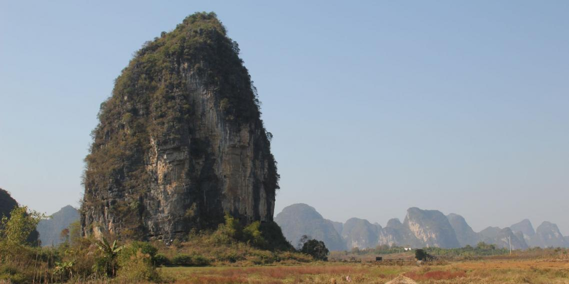 Climbers stand below The Egg, a karst in Yángshuò, Guăngxī, China.