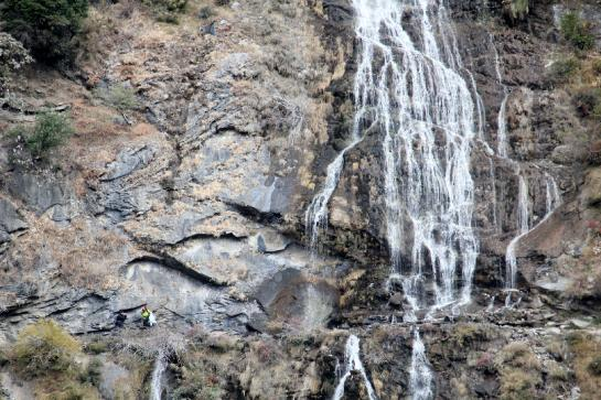 Hikers walk near a waterfall in in China's Tiger Leaping Gorge.