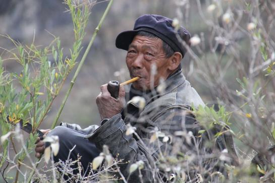 A Chinese farmer takes a break, smoking a pipe in China's Tiger Leaping Gorge.