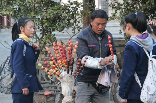 A man sells sugar-covered strawberries in Dàlǐ, China.