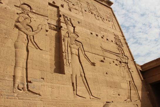 Carvings of Isis, Horus, and Osiris appear on the First Pylon of the Temple of Isis on Philae Island, Egypt.