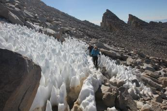 Hikers make their way through a field of snow towers.