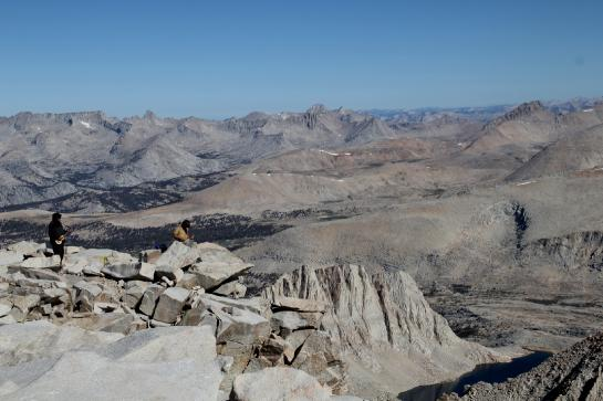 Men play a drum pad and a ukelele on the Mount Whitney summit.