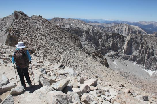 A hiker looks at the trail down from the Mount Whitney summit.