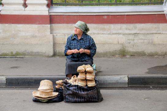 A Russian woman sells hats and shoes on a Moscow sidewalk.