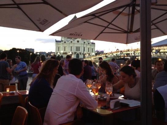 Beautiful people enjoy cocktails on the terrace of Strelka at Moscow's trendy Red October, a former chocolate factory. The Cathedral of Christ the Saviour and Patriarchiy Bridge can be seen in the distance.