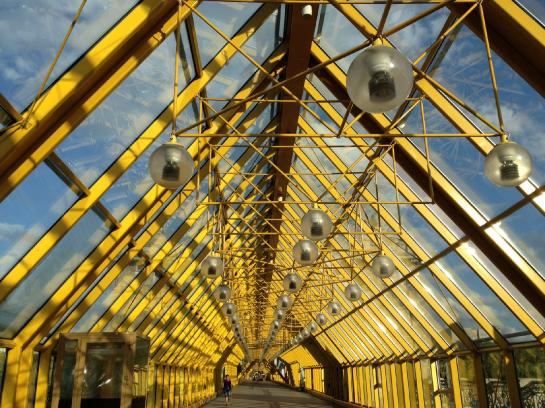 Bright yellow supports and industrial lights cover Andreyevsky (Andrew's) Bridge in Moscow.
