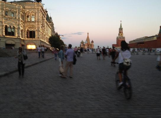 Olya rides her bicycle through Moscow's Red Square at twilight.