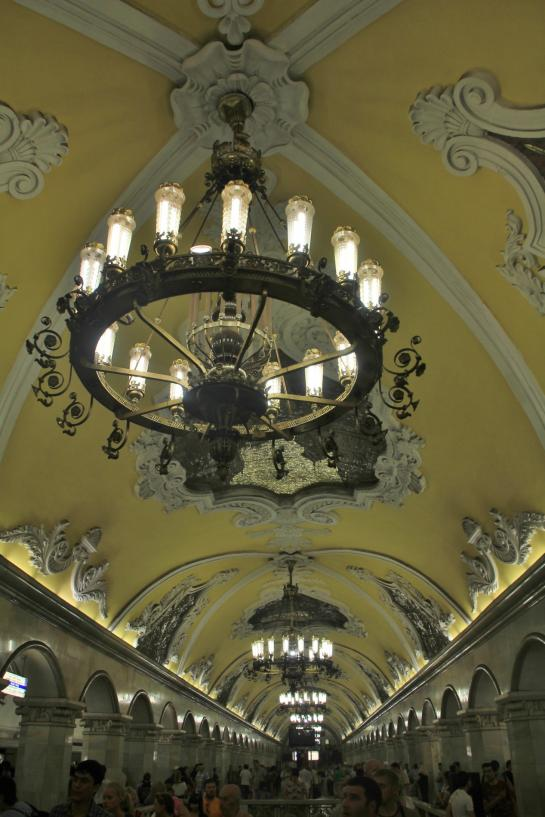 The Moscow Metro's Komsomolskaya Station features baroque design, Corinthian columns, arched yellow ceilings, and ornate chandeliers.