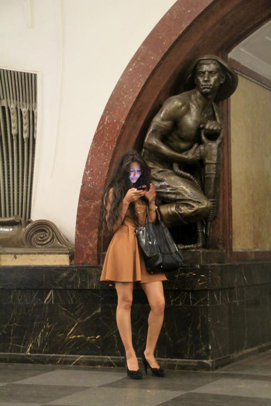A Russian woman sends a text under a bronze statue of a miner at the Ploshchad Revolyutsii Moscow Metro station.