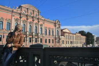 Nastya chats on a phone on Anichkov Bridge in St. Petersburg, Russia.