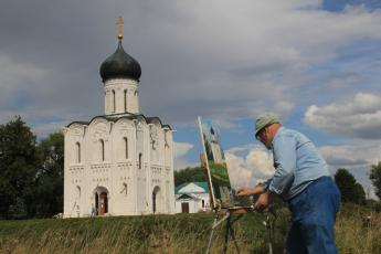 A Russian man paints the Church of the Intercession of the Holy Virgin on the Nerl River near Vladimir, Russia.