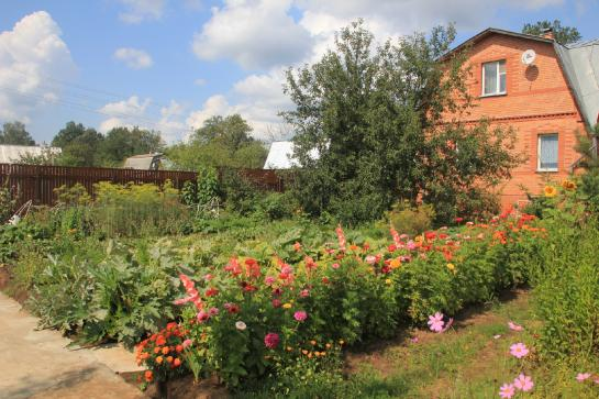 Flowers bloom in front a dacha, a typical Russian country home.
