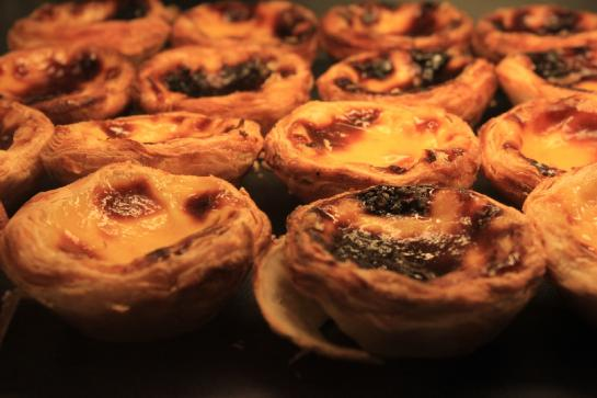 Pastéis de Belém, Portugal's famous custard egg tart, sit on a rack waiting to be purchased. (photo by Brian Leukart)