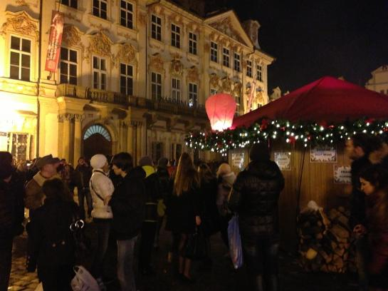 A lit Chinese skylantern settles onto a vendor's booth's awning in Prague's Old Town Square.