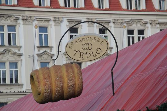 An enormous trdelnik hangs attached to a sign above a trdelnik vendor in Prague's Old Town Square.