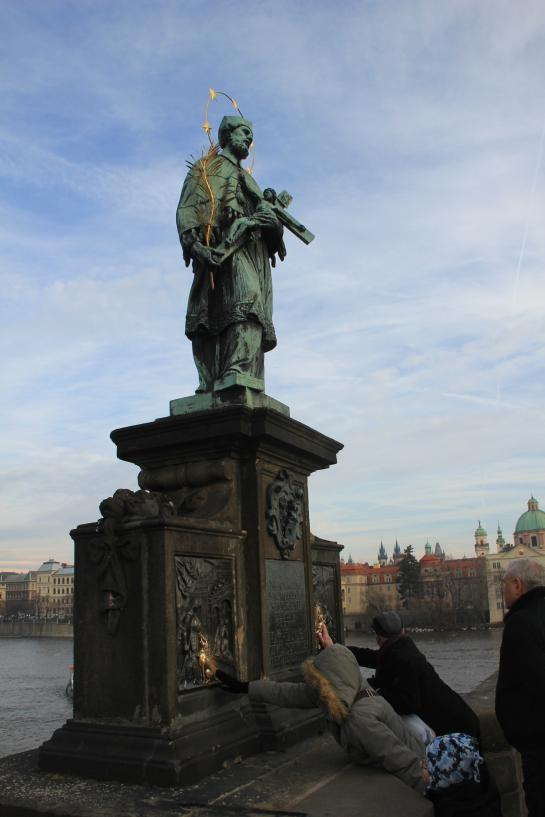 People touch, for good luck, the St. John of Nepomuk Statue on Prague's Charles Bridge.