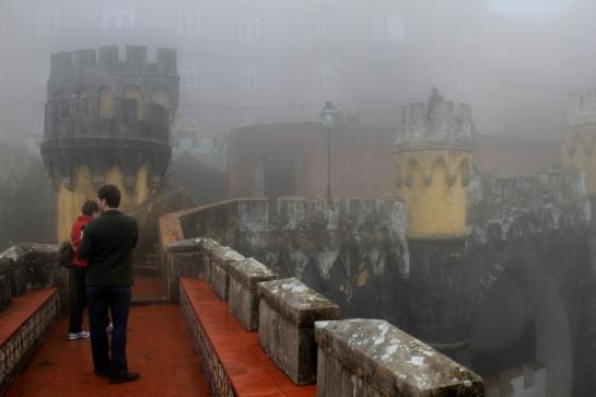 Tourists visit a fog-enveloped Pena National Palace in Sintra, Portugal.